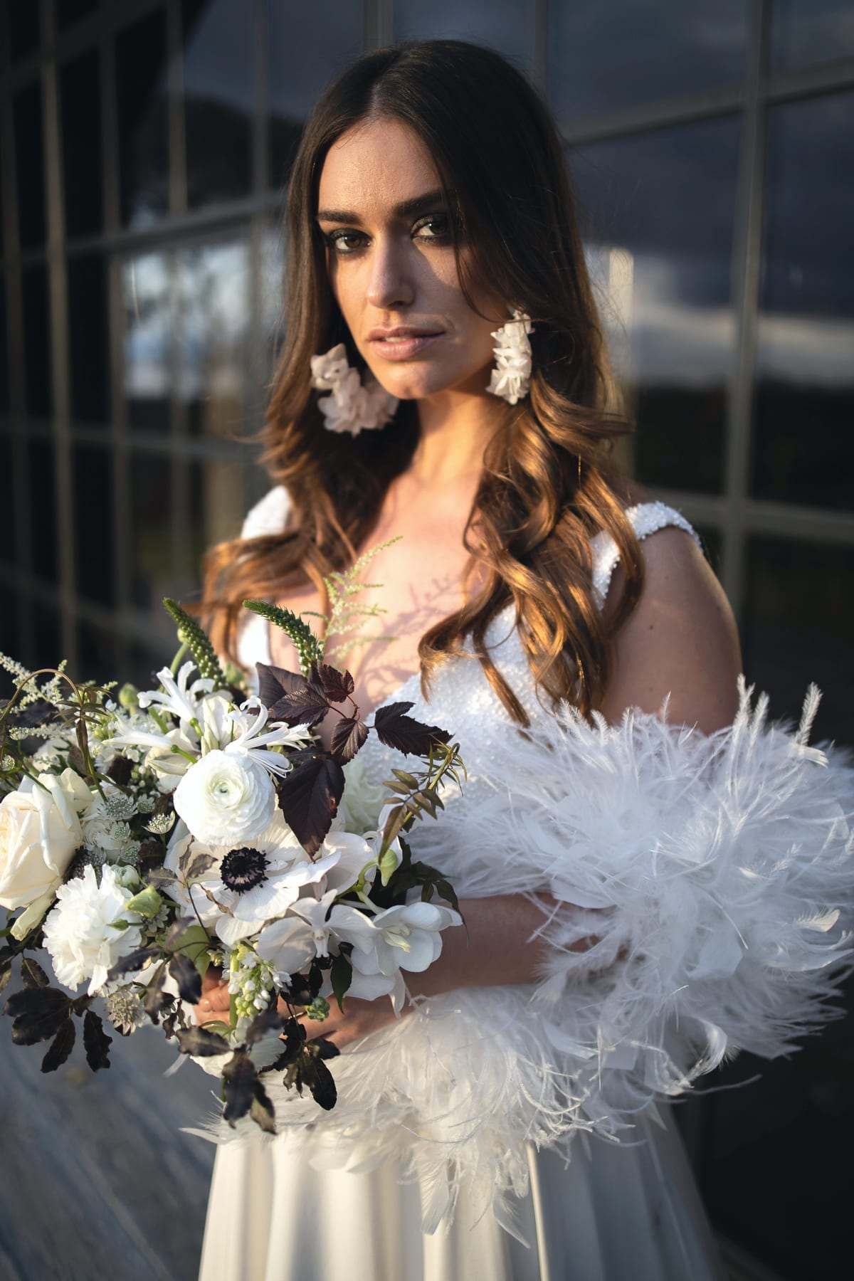 Close up of bride with feather boa and bouquet