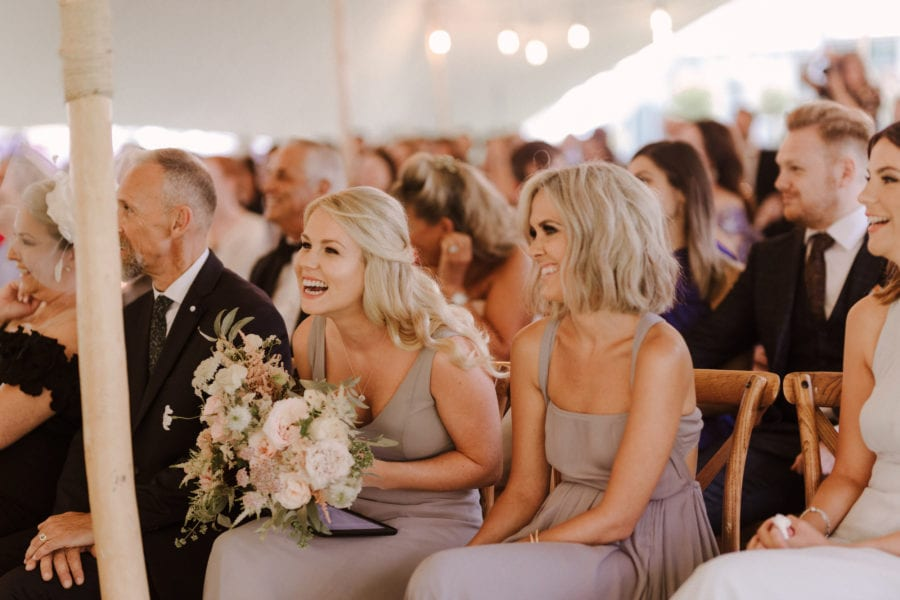 Laughing bridesmaids at outdoor wedding ceremony