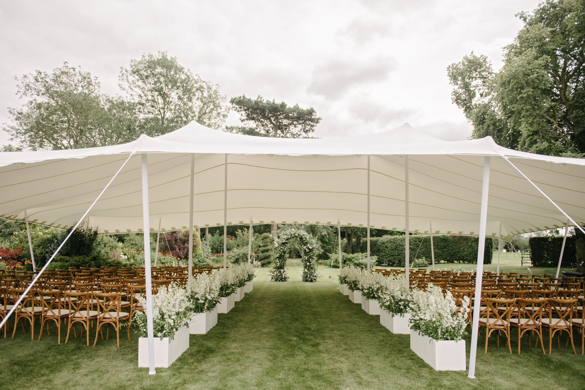 Stretch marquee set up for wedding ceremony in English garden
