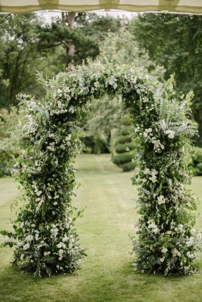 Glorious floral arch with abundance of greenery for wedding