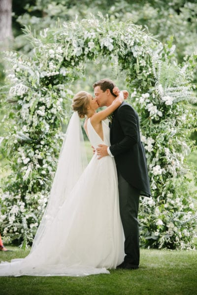 Bride and Groom kissing beneath arch of florals and greenery