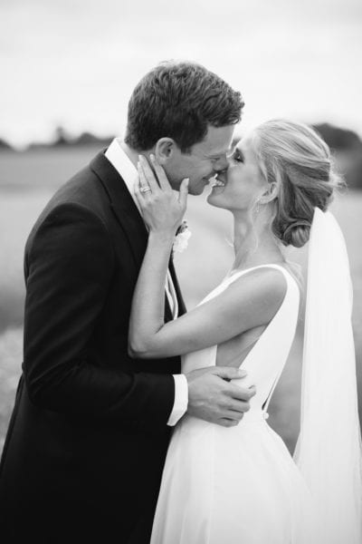 Black and white image of newly married couple kissing