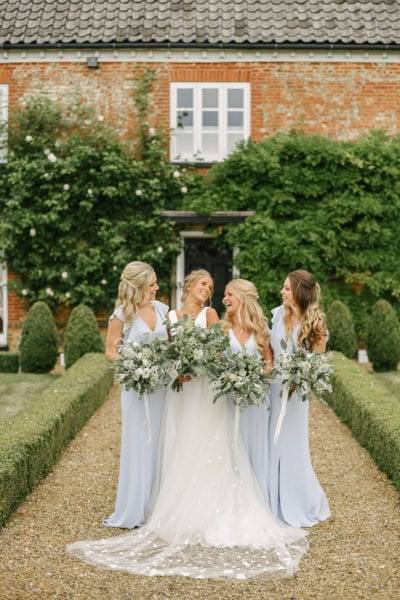 Bride with bridesmaids outside family home