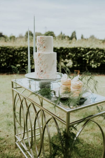 Wedding cake and small cakes for outdoor wedding lounge area