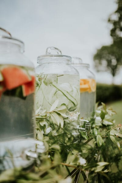 Close up of water dispensers with fruit and herbs for wedding